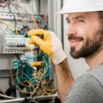 young professional electrician checking the switchboard