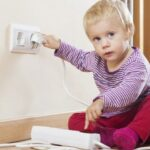 a small kid plugging in a electrical plug